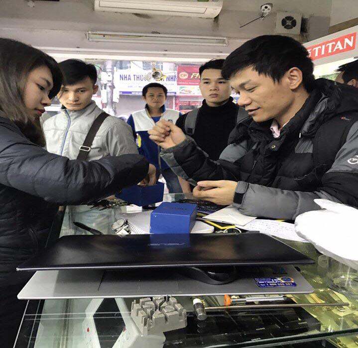 Nhân viên đang giúp khách hàng đeo chiếc đồng hồ vừa được lựa chọn